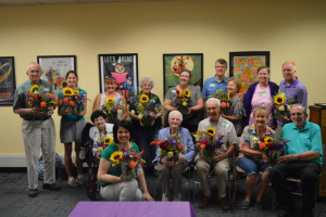The group shows off their flower arrangements